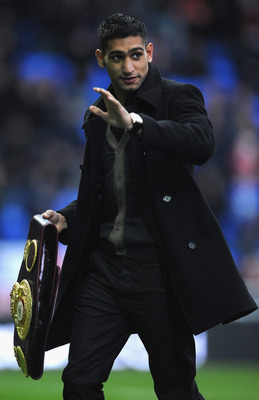 BOLTON, ENGLAND - DECEMBER 26:  Boxer Amir Khan shows his latest belt to the crowd during the Barclays Premier League match between Bolton Wanderers and West Bromwich Albion at Reebok Stadium on December 26, 2010 in Bolton, England.  (Photo by Laurence Gr