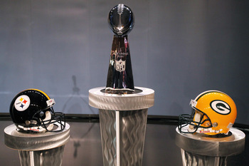 DALLAS, TX - FEBRUARY 04:  The Vince Lombardi Trophy is displayed between a Pittsburgh Steelers helmet and a Green Bay Packers helmet during a press conference with NFL commissioner Roger Goodell at the Super Bowl XLV media center on February 4, 2011 in D