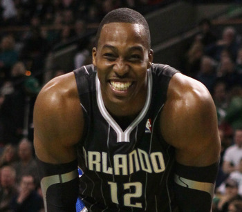 BOSTON, MA - JANUARY 17:  Dwight Howard #12 of the Orlando Magic smiles on the baseline as he waits for Shaquille O'Neal of the Boston Celtics to shoot a free throw on January 17, 2011 at the TD Garden in Boston, Massachusetts.  NOTE TO USER: User express