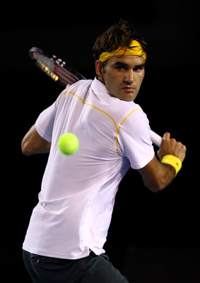 MELBOURNE, AUSTRALIA - JANUARY 27:  Roger Federer of Switzerland plays a backhand in his semifinal match against Novak Djokovic of Serbia during day eleven of the 2011 Australian Open at Melbourne Park on January 27, 2011 in Melbourne, Australia.  (Photo