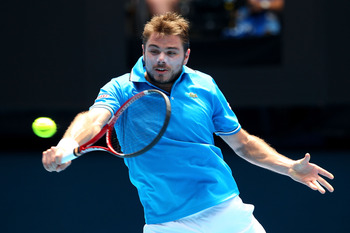 MELBOURNE, AUSTRALIA - JANUARY 25:  Stanislas Wawrinka of Switzerland plays a backhand in his quarterfinal match against Roger Federer of Switzerland during day nine of the 2011 Australian Open at Melbourne Park on January 25, 2011 in Melbourne, Australia