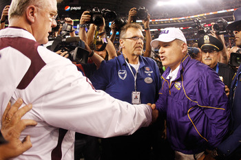 ARLINGTON, TX - JANUARY 07:  Head coach Les Miles of the Louisiana State University Tigers is congratulated by head coach Mike Sherman of the Texas A&M Aggies after the AT&T Cotton Bowl at Cowboys Stadium on January 7, 2011 in Arlington, Texas.  The Tiger
