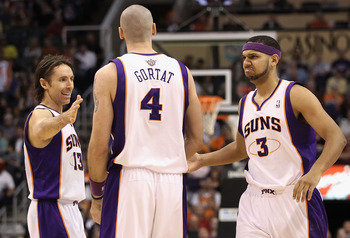 PHOENIX, AZ - JANUARY 30:  (L-R) Steve Nash #13, Marcin Gortat #4 and Jared Dudley #3 of the Phoenix Suns celebrate after scoring against the New Orleans Hornets during the NBA game at US Airways Center on January 30, 2011 in Phoenix, Arizona.  The Suns d