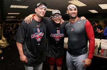 DENVER - SEPTEMBER 26:  (L-R) Matt Holliday, Yadier Molina and Albert Pujols of the St. Louis Cardinals celebrate clinching the National League Central Division after defeating the Colorado Rockies at Coors Field on September 26, 2009 in Denver, Colorado.
