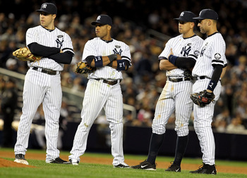 NEW YORK - OCTOBER 18:  Mark Teixeira #25, Robinson Cano #24, Alex Rodriguez #13 and Derek Jeter #2 of the New York Yankees look on during a pitching change against the Texas Rangers in Game Three of the ALCS during the 2010 MLB Playoffs at Yankee Stadium