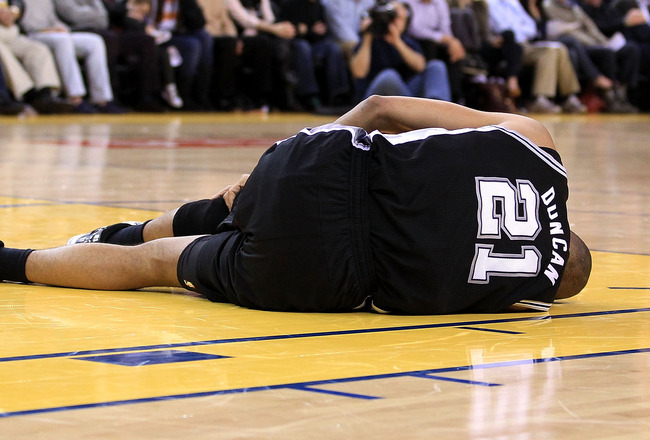 OAKLAND, CA - JANUARY 24:  Tim Duncan #21 of the San Antonio Spurs lies on the court after injuring his knee during their game against the Golden State Warriors at Oracle Arena on January 24, 2011 in Oakland, California.  NOTE TO USER: User expressly ackn