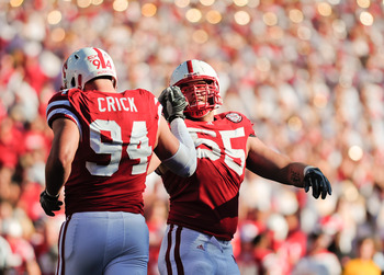 LINCOLN, NE - OCTOBER 30: Defensive tackle Baker Steinkuhler #55  of the Nebraska Cornhuskers high fives teammate  defensive tackle Jared Crick #94 after a third down stop during second half action of their game at Memorial Stadium on October 30, 2010 in