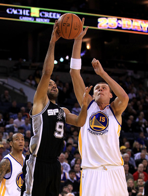 OAKLAND, CA - JANUARY 24:  Tony Parker #9 of the San Antonio Spurs goes up for a shot against Andris Biedrins #15 of the Golden State Warriors at Oracle Arena on January 24, 2011 in Oakland, California.  NOTE TO USER: User expressly acknowledges and agree