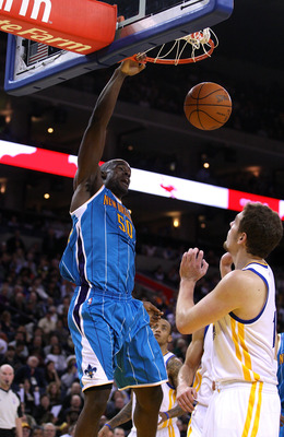 OAKLAND, CA - JANUARY 26:  Emeka Okafor #50 of the New Orleans Hornets dunks the ball over David Lee #10 of the Golden State Warriors at Oracle Arena on January 26, 2011 in Oakland, California.  NOTE TO USER: User expressly acknowledges and agrees that, b