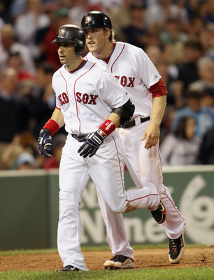 BOSTON - SEPTEMBER 08:  Lars Anderson #44 and Marco Scutaro #16 of the Boston Red Sox head for the dugout after both scored on Scutaro's home run against the Tampa Bay Rays on September 8, 2010 at Fenway Park in Boston, Massachusetts.  (Photo by Elsa/Gett