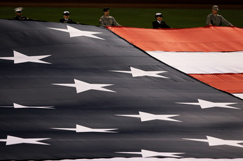 ARLINGTON, TX - OCTOBER 31:  Military personnel hold a giant flag during the performance of the National Anthem prior to the Texas Rangers playing against the San Francisco Giants in Game Four of the 2010 MLB World Series at Rangers Ballpark in Arlington