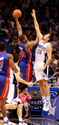 ORLANDO, FL - JANUARY 24:  Greg Monroe #10 of the Detroit Pistons attempts a shot over Ryan Anderson #33 of the Orlando Magic during the game at Amway Arena on January 24, 2011 in Orlando, Florida.  NOTE TO USER: User expressly acknowledges and agrees tha