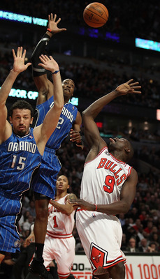 CHICAGO, IL - JANUARY 28: Dwight Howard #12 of the Orlando Magic leaps to block a shot by Loul Deng #9 of the Chicago Bulls as Hedo Turkoglu #15 defends at the United Center on January 28, 2011 in Chicago, Illinois. The Bulls defeated the Magic 99-90. NOT