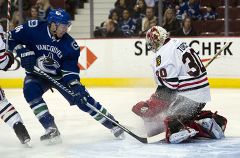 VANCOUVER, CANADA - JANUARY 4: Alexandre Burrows #14 of the Vancouver Canucks fails to get a handle on the loose puck after goalie Marty Turco #30 of the Chicago Blackhawks made a pad save during the second period in NHL action on February 04, 2011 at Rog