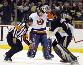 PITTSBURGH, PA - FEBRUARY 02:  Rick DiPietro #39 of the New York Islanders strips off his mask before mixing it up with Brent Johnson #1 of the Pittsburgh Penguins at Consol Energy Center on February 2, 2011 in Pittsburgh, Pennsylvania.  The Penguins shut
