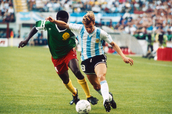 Argentinian footballer Claudio Caniggia is closely followed by the Cameroon player Benjamin Massing during their match at the 1990 World Cup in the Giuseppe Meazza stadium, Milan, 8th June 1990. (Photo by Getty Images)