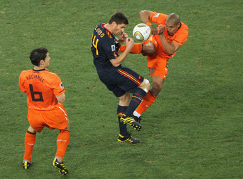 JOHANNESBURG, SOUTH AFRICA - JULY 11:  Nigel De Jong of the Netherlands tackles Xabi Alonso of Spain with a kick in the chest during the 2010 FIFA World Cup South Africa Final match between Netherlands and Spain at Soccer City Stadium on July 11, 2010 in