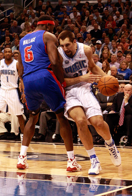 ORLANDO, FL - JANUARY 24:   Ryan Anderson #33 of the Orlando Magic drives against Ben Wallace #6 of the Detroit Pistons during the game at Amway Arena on January 24, 2011 in Orlando, Florida.  NOTE TO USER: User expressly acknowledges and agrees that, by