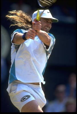 29 JUN 1993:  ANDRE AGASSI OF THE UNITED STATES PLAYS A TWO-HANDED BACKHAND DURING HIS QUARTER-FINAL MATCH AGAINST PETE SAMPRAS OF THE USA AT THE 1993 WIMBLEDON TENNIS CHAMPIONSHIPS. SAMPRAS WON THE MATCH AND PROCEEDED TO THE FINAL.