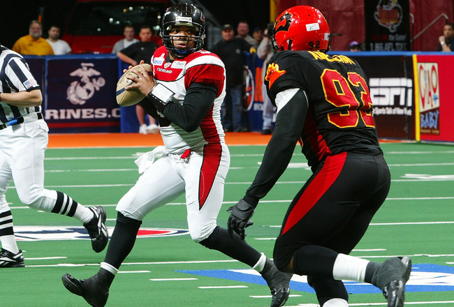 UNIONDALE, NY - APRIL 26:  Raymond Philyaw #9 of the Cleveland Gladiators looks to pass the ball against  Farouk Adelekan #92 of the New York Dragons on April 26, 2008 at Nassau Coliseum in Uniondale, New York.  Dragons defeat Gladiators 56-39  (Photo by