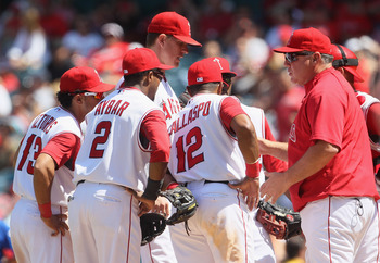 ANAHEIM, CA - AUGUST 11:  (L-R) Maicer Izturis #13, Erick Aybar #2, Jered Weaver #36 and Alberto Callaspo #12 of Los Angeles Angels of Anaheim meet with manager Mike Scioscia on the pitchers mound in the eighth inning against the Kansas City Royals at Ang