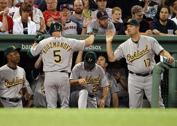 BOSTON - JUNE 02:  Kevin Kouzmanoff #5 of the Oakland Athletics is congratulated by manager Bob Geren #17 after Kouzmanoff hit a solo home run in the ninth inning against the Boston Red Sox on June 2, 2010 at Fenway Park in Boston, Massachusetts.  The Red