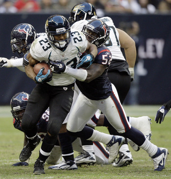 HOUSTON - JANUARY 02:  Running back Rashad Jennings #23 of the Jacksonville Jaguars is tackled by Xavier Adibi #52 of the Houston Texans at Reliant Stadium on January 2, 2011 in Houston, Texas.  (Photo by Bob Levey/Getty Images)