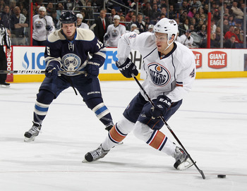 COLUMBUS, OH - FEBRUARY 05:  Taylor Hall #4 of the Edmonton Oilers tries to control the puck in front of Derek Dorsett #15 of the Columbus Blue Jackets at Nationwide Arena on February 5, 2011 in Columbus, Ohio.  (Photo by Gregory Shamus/Getty Images)