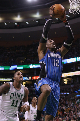 BOSTON, MA - FEBRUARY 06:  Dwight Howard #12 of the Orlando Magic takes a shot as Glen Davis #11 of the Boston Celtics defends on February 6, 2011 at the TD Garden in Boston, Massachusetts. The Celtics defeated the Magic 91-80. NOTE TO USER: User expressl
