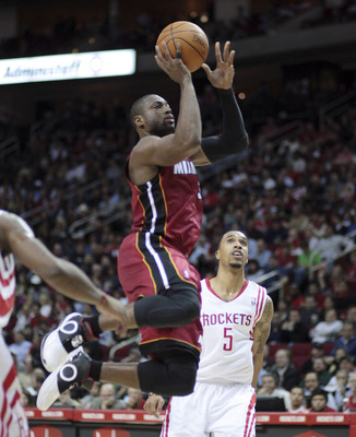 HOUSTON - DECEMBER 29:  Dwyane Wade #3 of the Miami Heat drives past Houston Rockets'  Courtney Lee #5 in the first half at Toyota Center on December 29, 2010 in Houston, Texas.  NOTE TO USER: User expressly acknowledges and agrees that, by downloading an