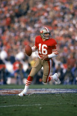 STANFORD, CA - JANUARY 20:  Quarterback Joe Montana #16 of the San Francisco 49ers runs with the ball as he looks downfield for a receiver in Super Bowl XIX against the Miami Dolphins at Stanford Stadium on January 20, 1985 in Stanford, California. The 49