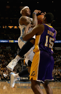 DENVER, CO - JANUARY 21:  Carmelo Anthony #15 of the Denver Nuggets is fouled by Ron Artest #15 of the Los Angeles Lakers at the Pepsi Center on January 21, 2011 in Denver, Colorado. The Lakers defeated the Nuggets 107-97. NOTE TO USER: User expressly ack
