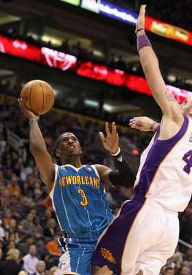 PHOENIX, AZ - JANUARY 30:  Chris Paul #3 of the New Orleans Hornets puts up a shot against Marcin Gortat #4 of the Phoenix Suns during the NBA game at US Airways Center on January 30, 2011 in Phoenix, Arizona.  NOTE TO USER: User expressly acknowledges an
