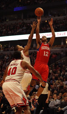 CHICAGO, IL - DECEMBER 21: Evan Turner #12 of the Philadelphia 76ers puts up a shot over Derrick Rose #1 and Kurt Thomas #40 of the Chicago Bulls at the United Center on December 21, 2010 in Chicago, Illinois. NOTE TO USER: User expressly acknowledges and