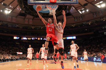 NEW YORK, NY - FEBRUARY 06:  Evan Turner #12 of the Philadelphia 76ers lays the ball up over Danilo Gallinari #12 of the New York Knicks at Madison Square Garden on February 6, 2011 in New York City. NOTE TO USER: User expressly acknowledges and agrees th