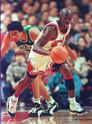 2 Mar 1996:  Guard Michael Jordan of the Chicago Bulls picks up the ball on a defensive rebound and starts running as guard Pervis Ellison of the Boston Celtics stumbles in the first quarter of their game at the United Center in Chicago.  The Bulls enter