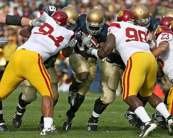 SOUTH BEND, IN - OCTOBER 17: Robert Hughes #33 of the Notre Dame Fighting Irish looks for running run against Armond Armstead #94 and DaJohn Harris #98 of the USC Trojans at Notre Dame Stadium on October 17, 2009 in South Bend, Indiana. USC defeated Notre