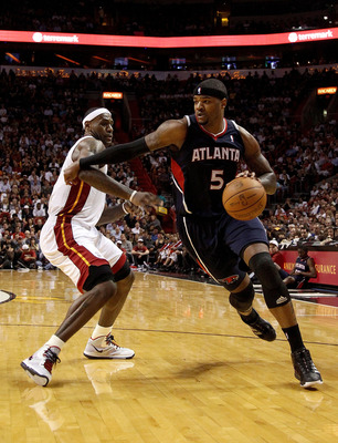MIAMI, FL - JANUARY 18: Josh Smith #5 of the Atlanta Hawks drives past LeBron James #6 of the Miami Heat during a game at American Airlines Arena on January 18, 2011 in Miami, Florida. NOTE TO USER: User expressly acknowledges and agrees that, by download