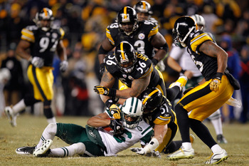 PITTSBURGH, PA - JANUARY 23:  Jeff Cumberland #86 of the New York Jets is tackled by James Farrior #51 and LaMarr Woodley #56 of the Pittsburgh Steelers during the 2011 AFC Championship game at Heinz Field on January 23, 2011 in Pittsburgh, Pennsylvania.