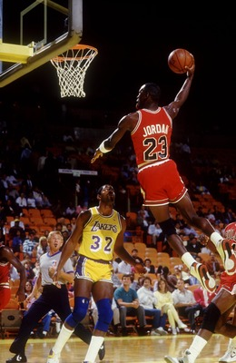 1980's:  CHICAGO GUARD MICHAEL JORDAN FLIES TO THE BASKET FOR A DUNK OVER LOS ANGELES GUARD MAGIC JOHNSON DURING THE BULLS GAME VERSUS THE BULLS AT THE GREAT WESTERN FORUM IN LOS ANGLELES, CALIFORNIA. Mandatory Credit: Rick Stewart/ALLSPORT