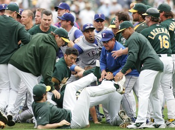 OAKLAND, CA - SEPTEMBER 16:   Dan Haren #15 of the Oakland Athletics falls to the ground during a bench-clearing brawl provoked after Nick Swisher #33 of the Oakland Athletics tackled Vicente Padilla #44 of the Texas Rangers after being hit by a pitch in