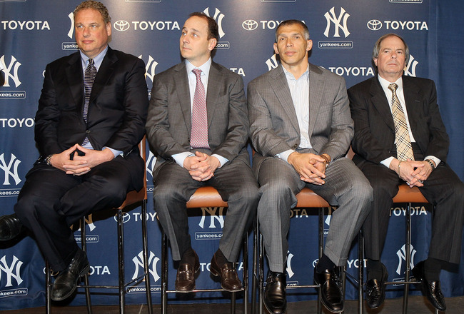 NEW YORK, NY - JANUARY 19:  (L-R) President Randy Levine, general manager Brian Cashman, manager Joe Girardi and COO Lonn Trost of the New York Yankees listen as Rafael Soriano (not pictured) speaks during his introduction press conference on January 19,
