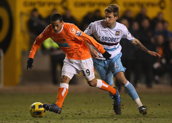 BLACKPOOL, ENGLAND - FEBRUARY 02:  DJ Campbell of Blackpool beats Rodoslav Kovac of West Ham United during the Barclays Premier League match between Blackpool and West Ham United at Bloomfield Road on February 2, 2011 in Blackpool, England.  (Photo by Ale