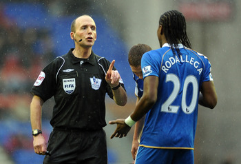 WIGAN, ENGLAND - FEBRUARY 05: Referee Mike Dean makes a point to Hugo Rodallega of Wigan Athletic during the Barclays Premier League match between Wigan Athletic and Blackburn Rovers at DW Stadium on February 5, 2011 in Wigan, England.  (Photo by Chris Br