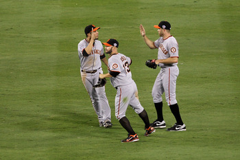 ARLINGTON, TX - OCTOBER 31:  (L-R) Andres Torres #56, Cody Ross #13 and Nate Schierholtz #12 of the San Francisco Giants celebrate in the outfield after their 4-0 win against the Texas Rangers in Game Four of the 2010 MLB World Series at Rangers Ballpark