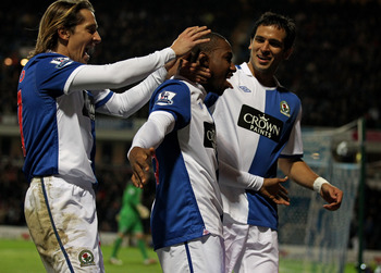 BLACKBURN, ENGLAND - JANUARY 23:  Junior Hoilett of Blackburn Rovers celebrates with his team mates Roque Santa Cruz and Michel Salgado (L) after scoring his team's second goal during the Barclays Premier League match between Blackburn Rovers and West Bro