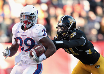 KANSAS CITY, MO - NOVEMBER 27:  James Sims #29 of the Kansas Jayhawks carries the ball as Jarrell Harrison #11 of the Missouri Tigers defends during the game on November 27, 2010 at Arrowhead Stadium in Kansas City, Missouri.  (Photo by Jamie Squire/Getty