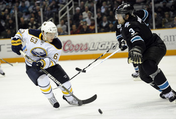 SAN JOSE, CA - JANUARY 6:  Tyler Ennis #63 of the Buffalo Sabres looks to get control of the puck in front of Douglas Murray #3 of the San Jose Sharks in the third period of an NHL hockey game at the HP Pavilion on January 6, 2011 in San Jose, California.