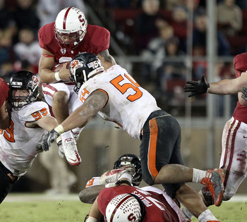 PALO ALTO, CA - NOVEMBER 27:  Tyler Gaffney #25 of the Stanford Cardinal jumps in the air as he is hit by Stephen Paea #54 and Gabe Miller #99 of the Oregon State Beavers at Stanford Stadium on November 27, 2010 in Palo Alto, California.  (Photo by Ezra S