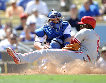 LOS ANGELES, CA - SEPTEMBER 01:  Domonic Brown #9 of the Philadelphia Phillies slides safely under the tag of Rod Barajas #28 of the Los Angeles Dodgers for a 5-1 lead during the ninth inning at Dodger Stadium on September 1, 2010 in Los Angeles, Californ